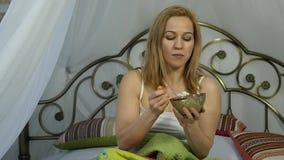 Het vrolijke meisje van de blondevrouw ontwaakte en etend een heerlijke salade op een bed, gezonde ontbijt langzame motie stock video