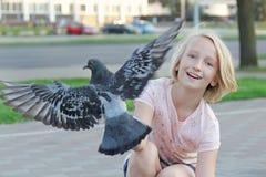 Het vrolijke meisje voedt duif op de straat in de stad Stock Foto's