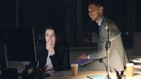 Het vrolijke mensenmeisje en de kerel vriendschappelijke medewerkers werken samen met computer in bureau die bij nacht spreken en stock videobeelden