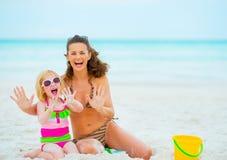Het vrolijke moeder en babymeisje spelen met zand Royalty-vrije Stock Fotografie