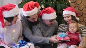 Het vrolijke mooie familiepaar en hun vrienden die met babymeisje zitten en haar verschillend geven stellen dichtbij Kerstmis voo stock video