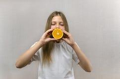 Het vrolijke mooie meisje houdt in de helften oranje helften Positieve emoties Gezond voedsel Veggie en Veganist stock foto's