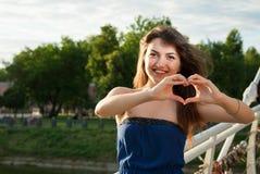 Het vrolijke mooie meisje toont symbool van het hart Stock Afbeelding
