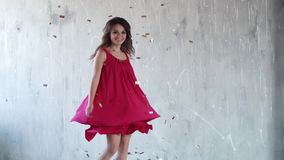 Het vrolijke onbezorgde meisje werpt op suikergoed en lacht meisje bij de partij Aantrekkelijke jonge vrouw in rode kleding Het m stock video