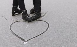 Het vrolijke paar die trok een hart in de sneeuw schaatsen royalty-vrije stock foto