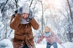Het vrolijke paar spelen met sneeuw in de winterbos Royalty-vrije Stock Afbeelding