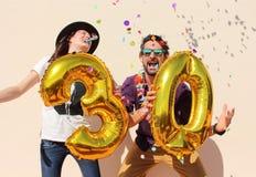 Het vrolijke paar viert een dertig jaar verjaardag met grote gouden ballons Stock Fotografie