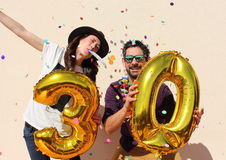Het vrolijke paar viert een dertig jaar verjaardag met grote gouden ballons Royalty-vrije Stock Foto's