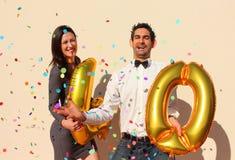 Het vrolijke paar viert een veertig jaar verjaardag met grote gouden ballons en kleurrijke kleine stukken van document in de luch Royalty-vrije Stock Foto's