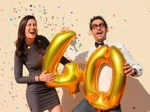 Het vrolijke paar viert een veertig jaar verjaardag met grote gouden ballons en kleurrijke kleine stukken van document in de luch Stock Foto