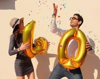 Het vrolijke paar viert een veertig jaar verjaardag met grote gouden ballons en kleurrijke kleine stukken van document in de luch Stock Foto's