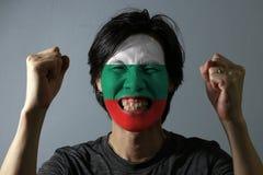 Het vrolijke portret van een mens met de vlag van Bulgarije schilderde op zijn gezicht op grijze achtergrond stock foto's