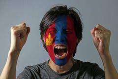 Het vrolijke portret van een mens met de vlag van Mongolië schilderde op zijn gezicht op grijze achtergrond stock fotografie