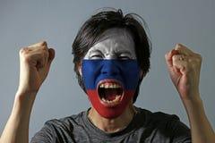 Het vrolijke portret van een mens met de vlag van Rusland schilderde op zijn gezicht op grijze achtergrond stock fotografie
