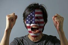 Het vrolijke portret van een mens met de vlag van de Verenigde Staten van Amerika schilderde op zijn gezicht op grijze achtergron royalty-vrije stock fotografie