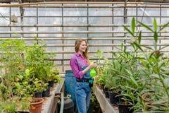 Het vrolijke positieve meisje bespuit installaties in de tuin royalty-vrije stock afbeelding