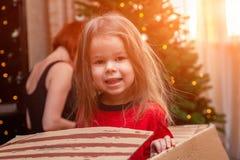 Het vrolijke schadelijke meisje stellen in doos van onder Kerstmis stock afbeelding