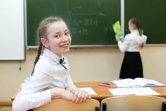 Het vrolijke schoolmeisje stelt in een les tevreden stock foto's