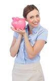Het vrolijke spaarvarken van de onderneemsterholding Stock Foto