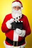 Het vrolijke stellen van Kris Kringle met clapperboard Royalty-vrije Stock Afbeelding