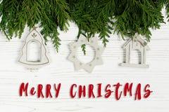 Het vrolijke teken van de Kerstmistekst op eenvoudig speelgoed op groene boomtakken Stock Foto