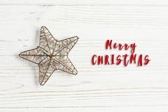 Het vrolijke teken van de Kerstmistekst op gouden ster op modieuze witte rusti Royalty-vrije Stock Foto's