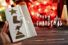 Het vrolijke teken van de Kerstmistekst op handholding verpakte huidig vakje o Royalty-vrije Stock Fotografie