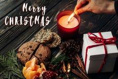 Het vrolijke teken van de Kerstmistekst op handverlichting op kaars en heden Royalty-vrije Stock Fotografie
