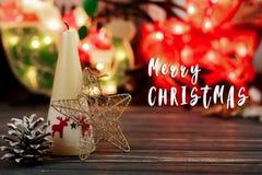 Het vrolijke teken van de Kerstmistekst op kaars en speelgoed op achtergrond van GA Stock Afbeeldingen