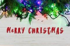 Het vrolijke teken van de Kerstmistekst op kader van slingerlichten op sparzemelen Stock Foto