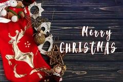 Het vrolijke teken van de Kerstmistekst op Kerstmis gouden modieus speelgoed op Re Royalty-vrije Stock Foto