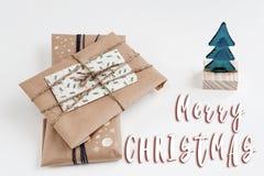 Het vrolijke teken van de Kerstmistekst op ornamentboom en giften in ambachtpa Royalty-vrije Stock Fotografie