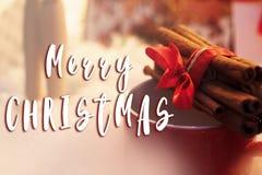 Het vrolijke teken van de Kerstmistekst op pijpjes kaneel met lint op rood Royalty-vrije Stock Afbeeldingen