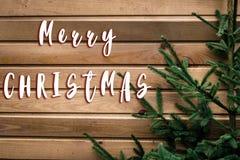 Het vrolijke teken van de Kerstmistekst op de verse groene takken van de Kerstmisboom Stock Fotografie
