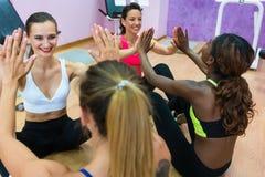 Het vrolijke vrouw slaan dient training tijdens groepsklasse in stock afbeeldingen