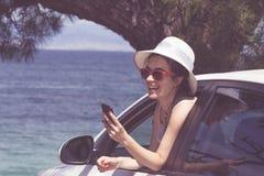 Het vrolijke vrouwelijke leunen op autoraam en het gebruiken van slimme telefoon royalty-vrije stock foto