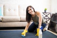 Het vrolijke vrouwen schoonmakende tapijt met hulp van blauwe borstel en schrikt af stock fotografie