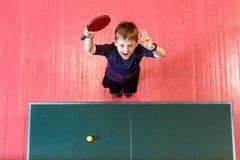 Het vrolijke zeven-jaar-oude kind geniet van winnend pingpong, hoogste mening groene pingponglijst stock fotografie