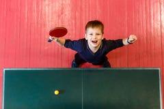 Het vrolijke zeven-jaar-oude kind geniet van winnend pingpong, hoogste mening stock fotografie
