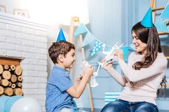 Het vrolijke zoon en moeder vechten met stuk speelgoed robots Royalty-vrije Stock Fotografie
