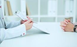 Het vrouwelijke aanvraagformulier van de artsenholding terwijl het raadplegen van patiënt Royalty-vrije Stock Fotografie