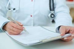 Het vrouwelijke aanvraagformulier van de artsenholding terwijl het raadplegen van patiënt Royalty-vrije Stock Afbeeldingen
