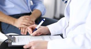 Het vrouwelijke aanvraagformulier van de artsenholding terwijl het raadplegen van mensenpatiënt in het ziekenhuis Geneeskunde en  stock foto's