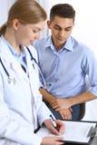 Het vrouwelijke aanvraagformulier van de artsenholding terwijl het raadplegen van mensenpatiënt in het ziekenhuisbureau Geneeskun stock afbeeldingen