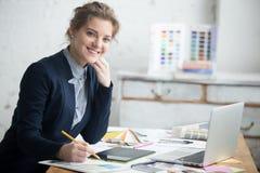 Het vrouwelijke architect stellen in bureau stock foto's
