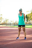 Het vrouwelijke atleet uitrekken zich op een renbaan Stock Fotografie