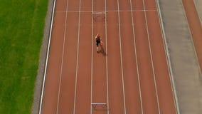 Het vrouwelijke atletische springen over hindernis op sportenspoor stock videobeelden