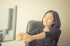 Het vrouwelijke Aziatische beambte uitrekken zich uit na lang werkuur stock afbeelding