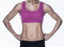 Het vrouwelijke bodybuilder stellen met handen op heupen medio sectie Stock Foto