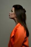 Het vrouwelijke brunette van de manierschoonheid met rode lippen en oranje jasje Stock Afbeelding